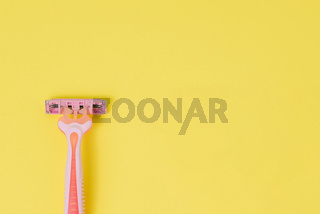 Female razor for depilation on a yellow background. Pink disposable razor. Top view, copy space.