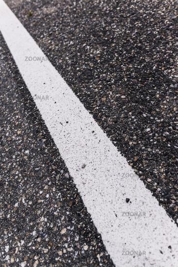 Old asphalt road with separation line. Selective focus.