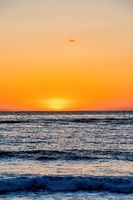 Dark ocean and orange sky at the horizon during sunset at San Diego California