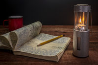 vintage expedition journal with candle lantern