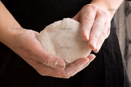 Dough in chef's hands.