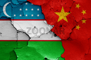 flags of Uzbekistan and China painted on cracked wall