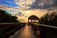 Tiki hut Boardwalk leads down to the white sand of Barefoot Beach in Bonita Springs