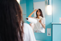 Portrait of young woman using hairdryer in bathroom