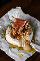 Baked camembert with nuts and honey, fig and thyme slices.