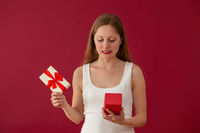 Embarrassed woman looking on a present on red background
