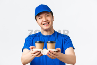 Online orders, takeaway and employees concept. Close-up of cute smiling male courier in blue uniform cap and t-shirt, handing coffee to customer, standing white background