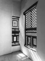 Black and white of Corner of two Interleaved wooden ornate windows - Mashrabiya - in stone wall