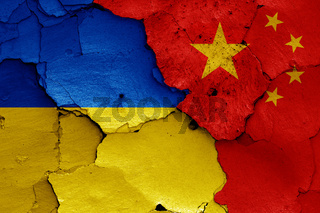 flags of Ukraine and China painted on cracked wall
