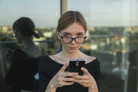 Young business woman uses phone. Good looking brunette female uses online banking on smart phone to transfer money from credit card. Girl using smart phone and chatting with business partners.