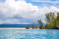 Big Clouds Over Sandspit in a Tropical Bay and an Old Hut in the Jungle