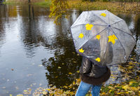 woman under umbrella stands on the shore of an autumn lake