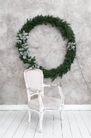 Christmas interior of the room. Gray chair stands under a light wall on which hangs a Christmas wreath. Green conifer wreath decorated with silver leaves and garland. High quality photo