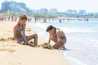 Girls on the seashore make sand castles