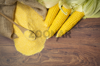 Ripe young sweet corn cob spoon and cornmeal from above