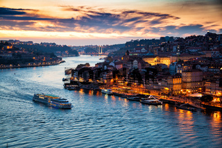 Porto, Portugal: Evening view of Porto cityscape and the Douro River with traditional Rabelo boats, seen from the Dom Luis bridge after sunset