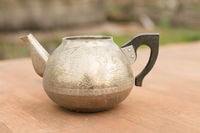 an old metal teapot without a lid. silver color