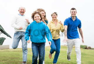 Smiling family running in the grass