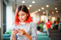 Portrait of a red hair young casual woman looking at mobile phone - Student girl paying attention to timetable on smartphone