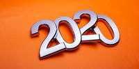 Happy New Year 2020. Symbol from number 2020 on orange background. Silver letters in the form of numbers 2020.
