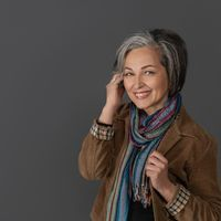Creative mature woman in casual touching her graying short hair. Studio portrait on gray background. Copy space at left