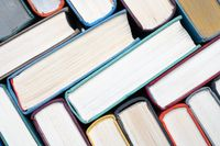Stack of hardcover books on bookshelf. Close-up view of vintage hardback books as background