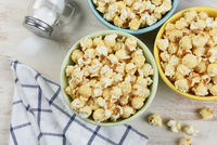 High angle shot of three different colored bowls of fresh popped popcorn with towl and salt shaker with salt spilling out.