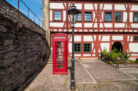Half-timbered house with red call-box and black street lamp in the foreground