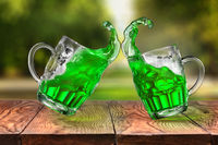 Splashes of fresh green beer in two jumping glasses.
