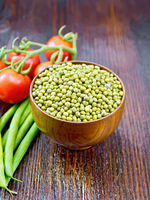 Mung beans  in bowl with vegetables on dark wooden board
