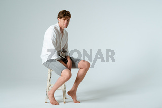 Portrait of young man full length sitting on chair and looking at camera isolated on white background. Copy space