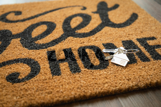 New House Keys and Keychain Rests on Home Sweet Home Welcome Mat