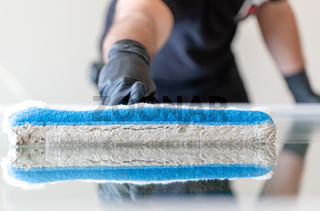 professional window cleaner using a window cleaning washer sleeve to cleanse a large fold down apartment window