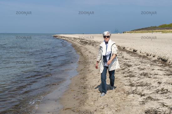 Elderly woman walks on the beach of the Baltic Sea