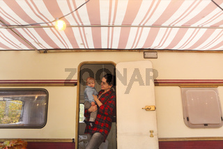 Smiling happy mother with baby son in the house on wheels
