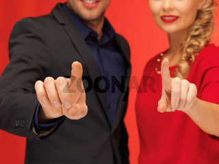 man and woman pressing virtual button