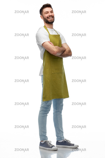 happy barman or waiter in apron with crossed arms