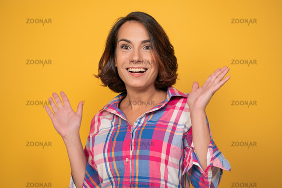 Enthusiastic woman raising up her hands. Smiling young brunette in casual cut out on yellow background