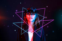 Mixed reality girl wearing hololens glasses under neon light on sparkling galaxy background. Virtual reality combine augmented reality concept.