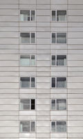 close up of a grey modern concrete highrise building with geometrical metallic cladding and repeating windows