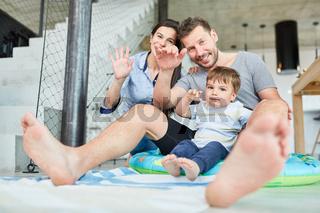 Familie mit Kleinkind winkt glücklich im Wohnzimmer