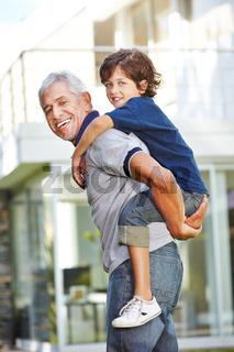 Großvater trägt Enkel huckepack