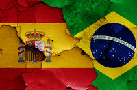 flags of Spain and Brazil painted on cracked wall