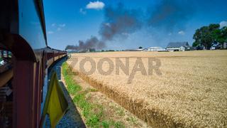 Steam Passenger Train Traveling Along Wheat Field