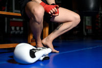 Closeup of boxer legs resting on bench in gym after training.