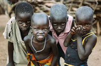 TOPOSA TRIBE, SOUTH SUDAN - MARCH 12, 2020: Boys in tattered dirty clothes looking at camera on blurred background of Toposa Tribe village in South Sudan, Africa