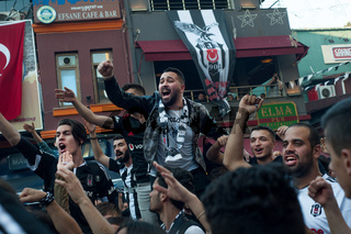 Besiktas Carsi football supporters singing songs before a match in Istanbul, Turkey.