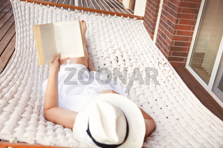 Woman lying in hammock and reading book