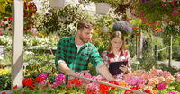 Two Gardeners doing paperwork between plants