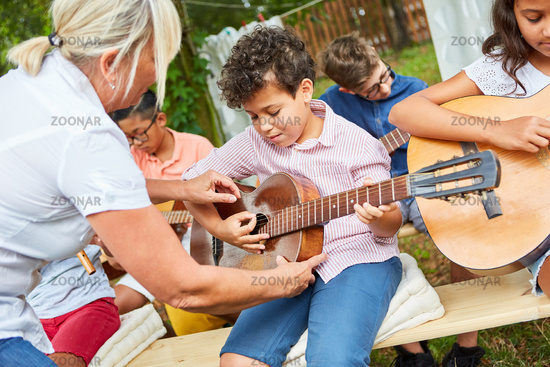 Teacher helps child learn to play guitar